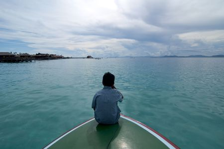 A boy takes a rest in front of boat during vacation into tropical island