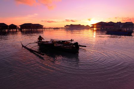 Fisherman prepares his traditional boat during sunset at the coastal of beauty tropical island Stock Photo