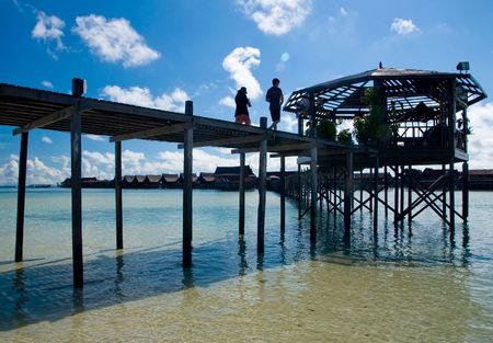 Tourist couples in shilouttee walk on man-made walkway exotic tropical resort of Kapalai island Stock Photo - 5314865