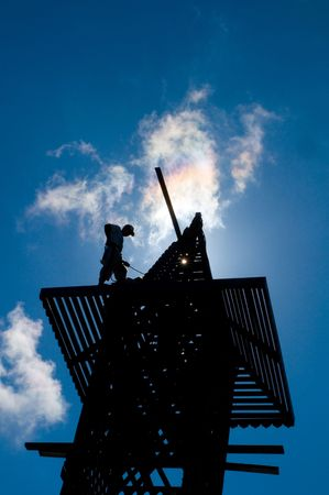 Worker in shilouttee repairs the tower of Kapalai island tropical resort photo