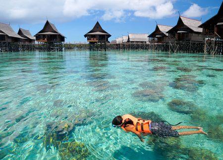 休暇中にサンゴとクリア クリスタル海塗りつぶしに少年泳ぐ