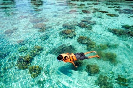 A boy swims on clear crystal ocean fills with coral during vacation