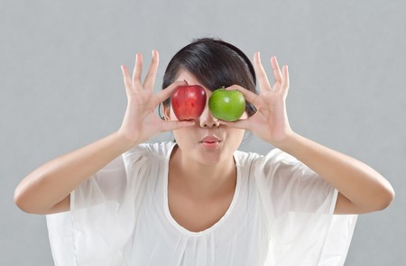 young pretty girl shows an expression with red and green apples photo