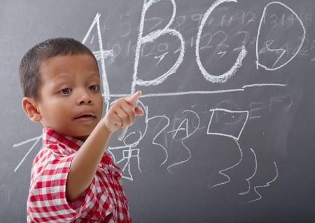 A little boys writes ABC on blackboard