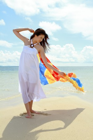Asian pretty girl plays with colorful sarong at beach during holiday photo