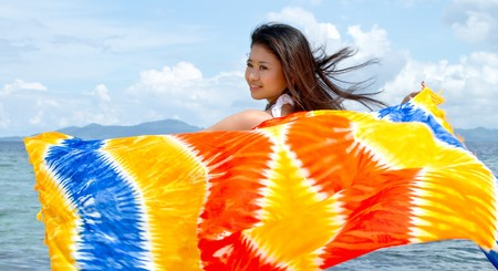 Asian pretty girl plays with colorful sarong at beach during holiday Stock Photo