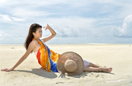 Asian pretty girl lays on beach during holiday at beautiful ocean