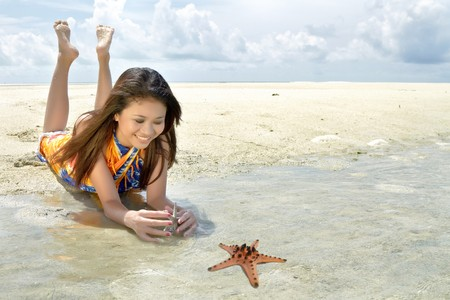 Asian pretty girl plays with starfish during holiday at beautiful ocean Stock Photo