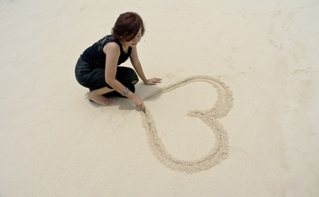 Pretty girl draws love shape on sand during holiday