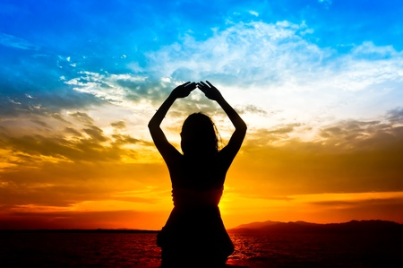 Silhouette of woman performs as yoga exercise on the beach during sunset photo