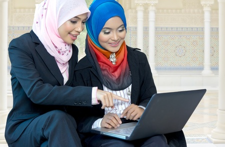 Young Asian muslim girls discuss with laptop photo