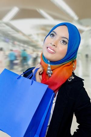 middle eastern clothing: Ragazza musulmana con la borsa della spesa in ipermercato con sfocatura dello sfondo