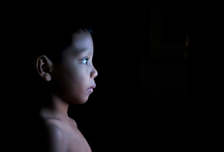television remote: Boy watching static on television in the dark