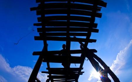 Silhouet van de mens lopen op kapotte brug