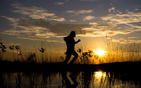 Silhouette of young woman running during sunset