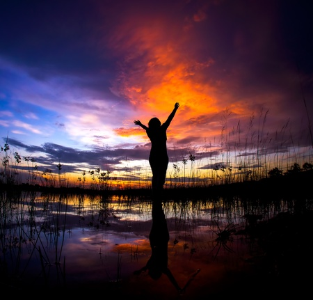 Silhouette of young woman during colorful sunset Stock Photo