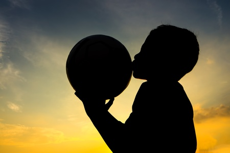 Boy kiss the ball during sunset Stock Photo