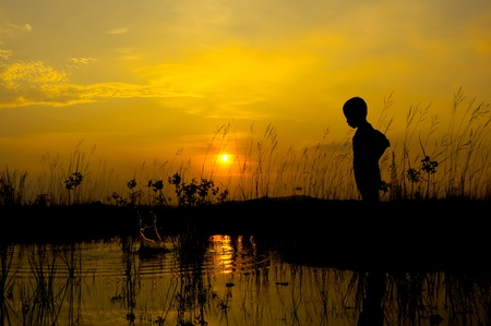 Little boy throw a stone on pond at sunset