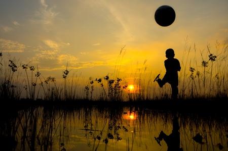 Boy kicks the ball during sunset