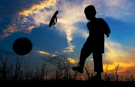 Boy kicks the ball during sunset photo