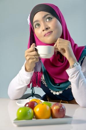 femmes muslim: Belles femmes musulmanes ayant pause-caf� avec des fruits sains Banque d'images