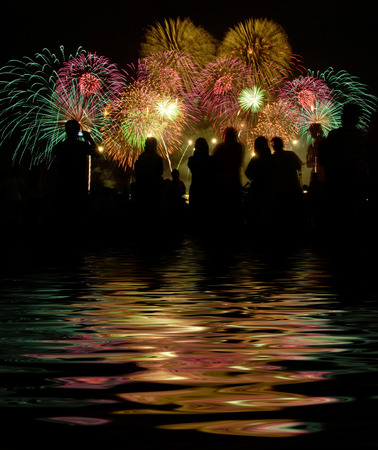 people stand watching for firework shows. digital compositing, colour tone, water reflection and ripple effects.
