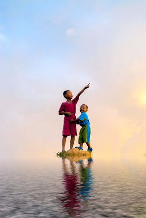 Kids stand in the middle of rock surrounding of water. digital compositing with colour tone, water reflection and ripple effects. Stock Photo