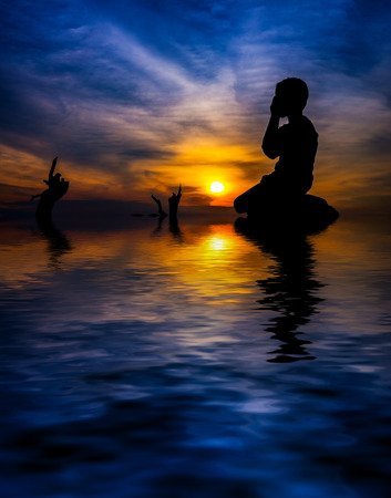 kid in silhouette stand prays during sunset. digital compositing with colour tone, water reflection and ripple effects.