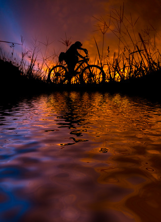 man with bicycle reflected on lake during sunset Stock Photo