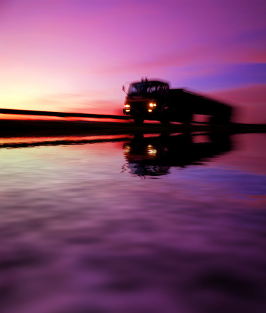 lorry at highway during sunset reflected on water. motion blur effects.