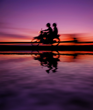 motorcyclist at highway during sunset reflected on water. motion blur effects. Stock Photo