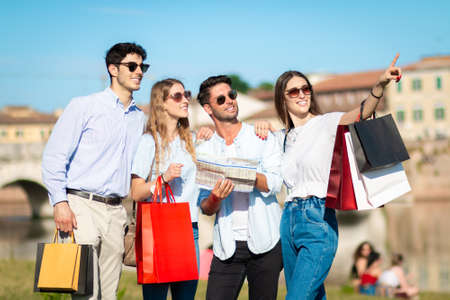group of tourists friends making shopping and visiting - four young person with shopping bag and map