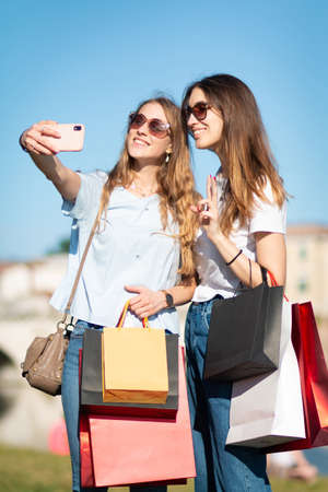 two young tourist girl enjoy shopping and selfie - girlf friend take selfie after shopping
