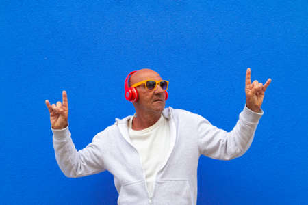 senior man listen music and have fun making rock gesture on blue background - portrait on colored background of elderly man listening to music with headphones and having fun - concept about crazy retired Stock fotó - 153223908