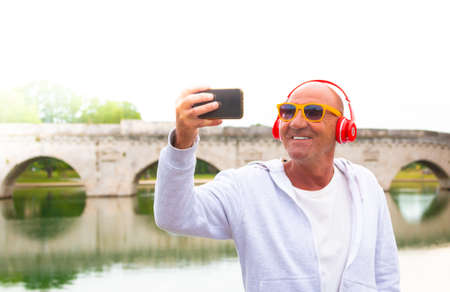 senior man takes a selfie and smiles listening to music with headphones - old man takes a selfie outdoor - concept about happy retirement