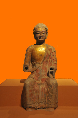 qi: Painted gold stone statue of Buddha North Qi Editorial