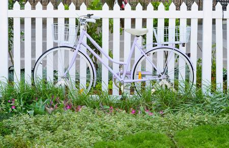 cerca blanca: bicycl magro en la cerca blanca de las mujeres de color p�rpura Foto de archivo