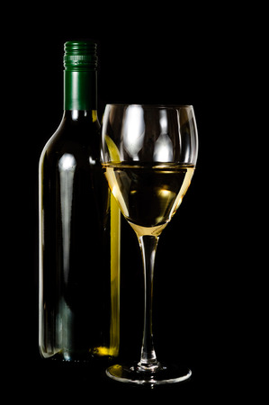 A glass and green rit bottle of white wine on dark background