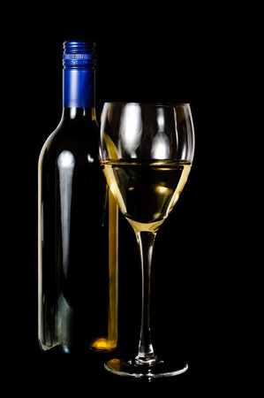 A glass and blue rit  bottle of white wine on dark background