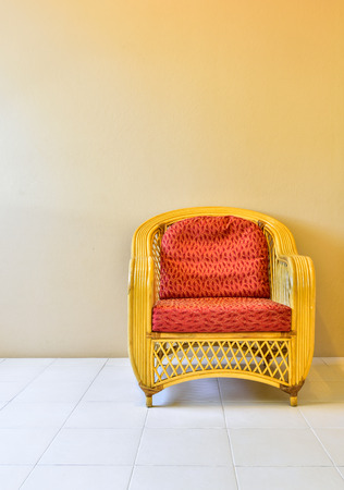 elbow chair: Yellow rattan armchair in room, background