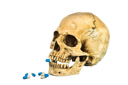eye socket: Side view of human skull with pill in teeth on white background