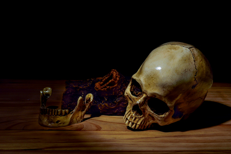 shadowy: Dark and shadowy human skull in a pool of light and dark background