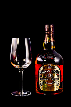 scotch whisky: SYDNEY, AUSTRALIA - February 9, 2016: Bottle of Chivas Regal on black background, Chivas Regal  Blended Scotch Whisky aged twelve years. Chivas Regal is a premium Blended Scotch Whisky produced by Chivas Brothers since 1801 Editorial