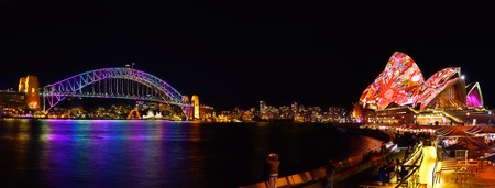 bridged: SYDNEY, AUSTRALIA - May 29, 2016, Panorama of Sydney Opera House and harbour bridged illuminated with colourful light design imagery, during the Vivid Sydney 2016 annual public event.