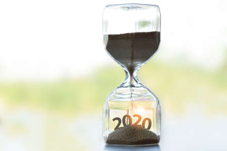 The hourglass placed on the table tells the time of year 2020 is about to begin. happy New Year. With copy space
