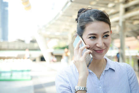 A beautiful Western woman uses her smartphone to talk outdoors. She smiles happily. Technology, Mobile Phone Application. Business Concept, Work or Communication. With copy space