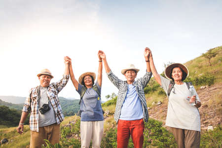 A group of Asian seniors hiking and standing on high mountains enjoying nature. Senior community concepts Zdjęcie Seryjne