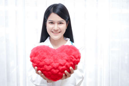 A beautiful Asian woman doctor holding a big red heart. In the treatment room. Hospital patient care concepts