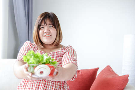 Fat Asian women carry a cup of salad greens to eat to lose weight and make them healthy. The concept of food to reduce belly fat without disease. with copy space.