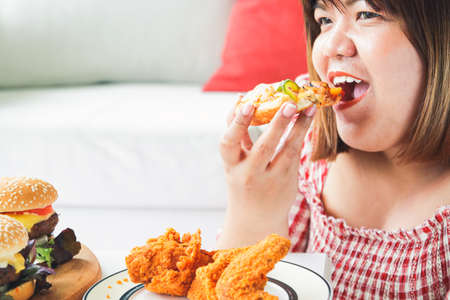An Asian fat woman is eating pizza and fried chicken on the sofa in her house. The concept of consuming food that causes disease is not good for health Archivio Fotografico